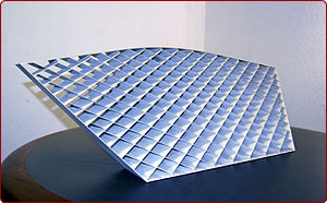 Flight Grids are EDMed on compound angles. We start with a 220-lb. plate of aluminum. When the part is complete, it weighs just 1.6 pounds.